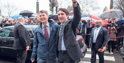 Prime Minister Justin Trudeau, right, waves to city staff and members of the public as he's welcomed by Mayor Gregor Robertson for a visit to City Hall in Vancouver, B.C., on Thursday December 17, 2015. Trudeau's visit to Vancouver City Hall was the first by a prime minister since his father, former prime minister Pierre Trudeau visited in 1973. THE CANADIAN PRESS/Darryl Dyck